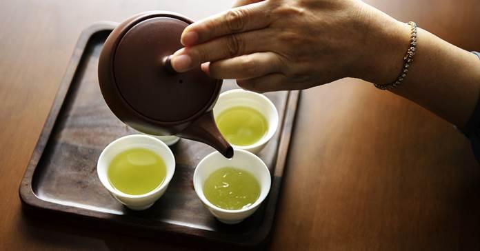 Čovek sipa zeleni čaj u šolju