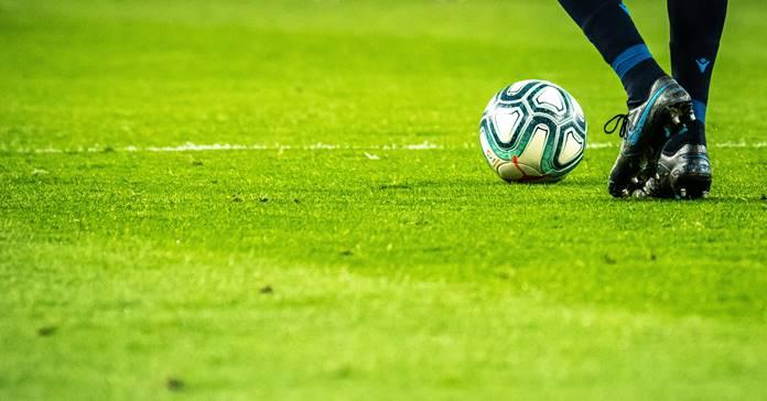 Fudbalska lopta na travnatom fudbalskom terenu