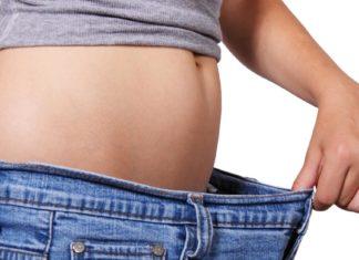 Devojka sa ravnim stomakom drži pantalone koje su joj široke u struku