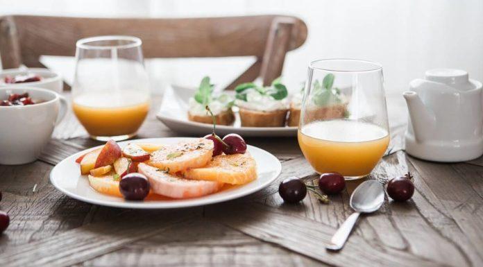 čaša sa sokom i hrana u tanjiru, na drvenom stočiću