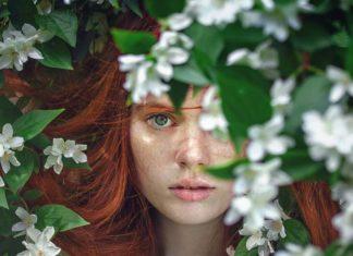 Riđa devojka sa pegama među cvećem