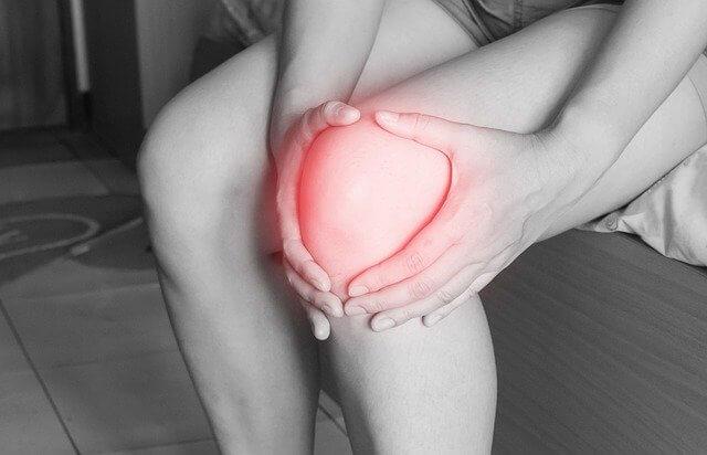 Devojka se drži za koleno - bol u kolenu