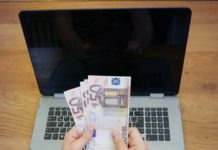 Ruka u kojoj je novac iznad laptopa