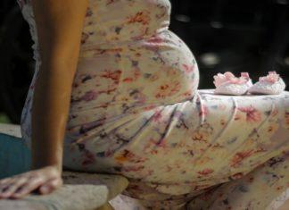 Trudnica koja sedi na krevetu u haljini