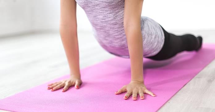 Žena radi jogu na prostirci